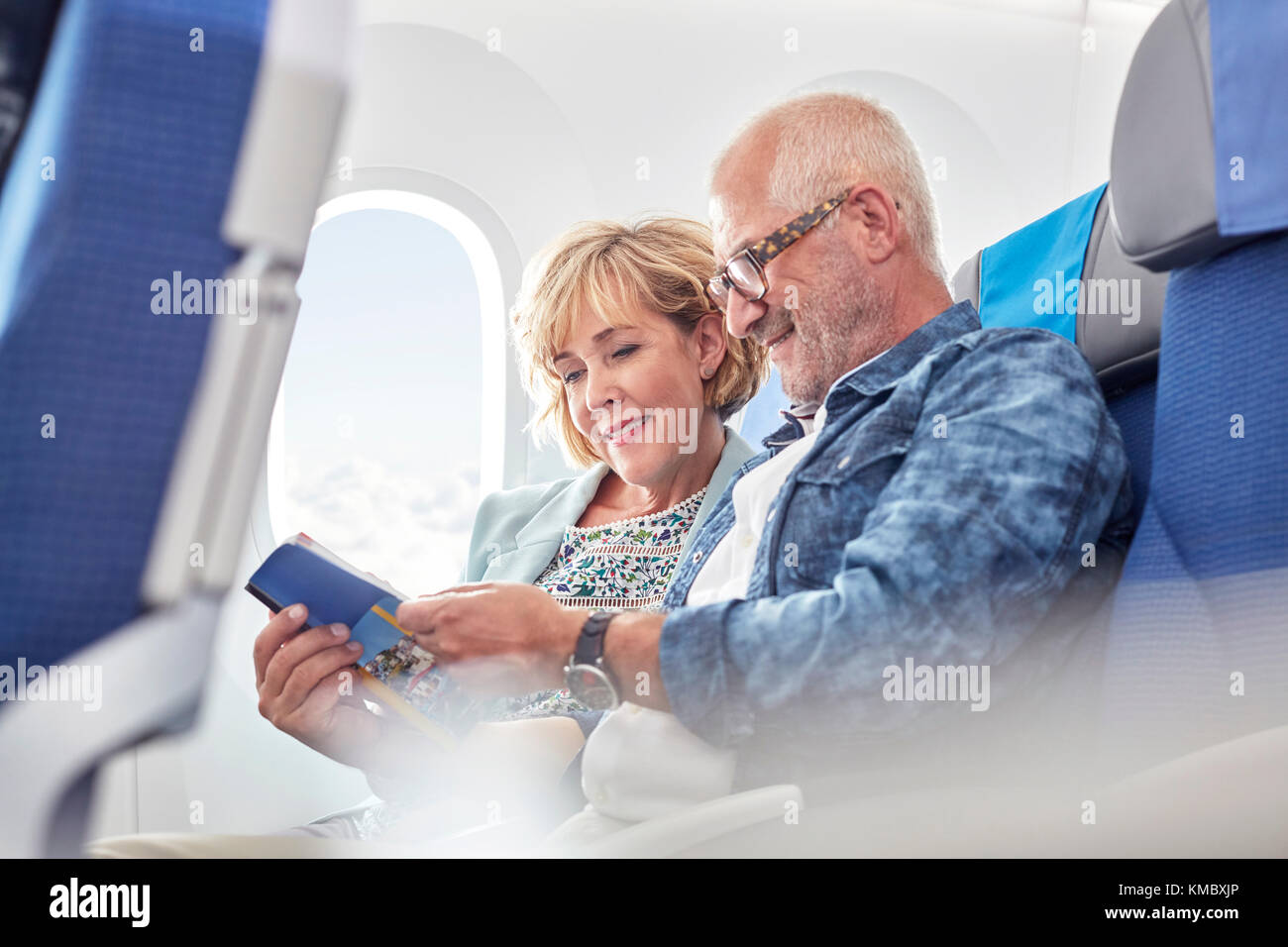 Mature couple reading guidebook on airplane - Stock Image