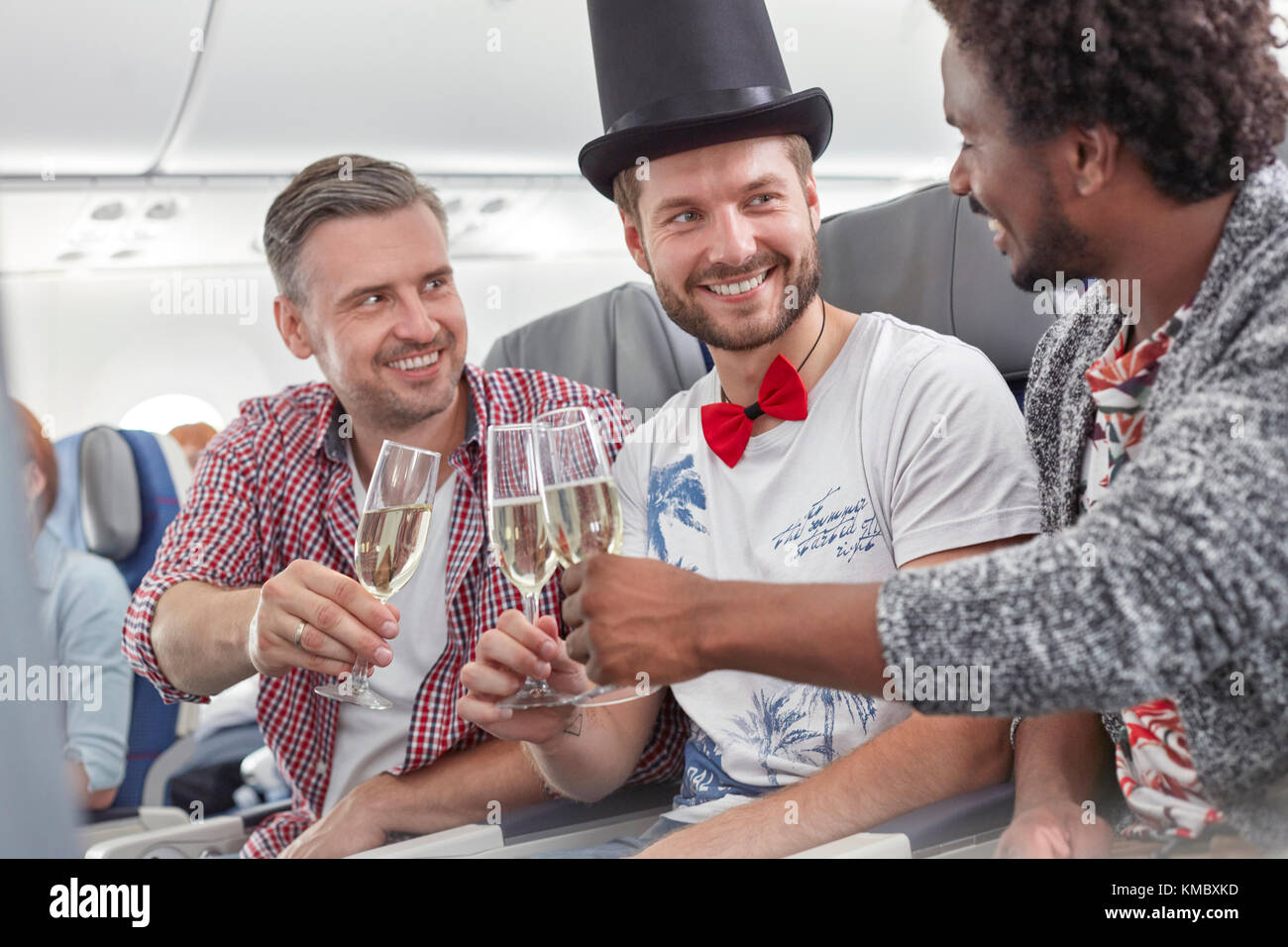 Young male friends toasting champagne glasses on airplane - Stock Image