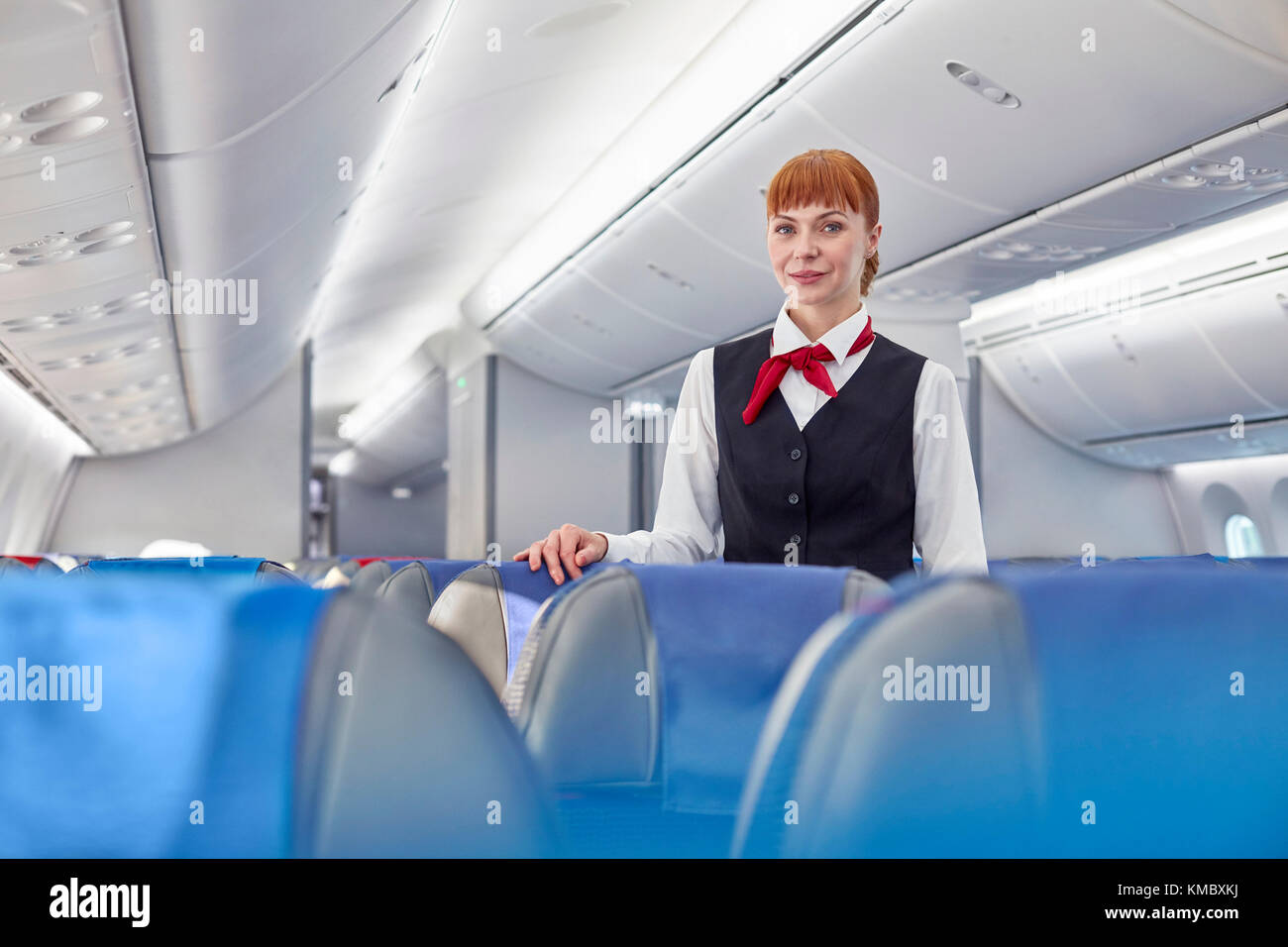 Portrait confident female flight attendant on airplane - Stock Image