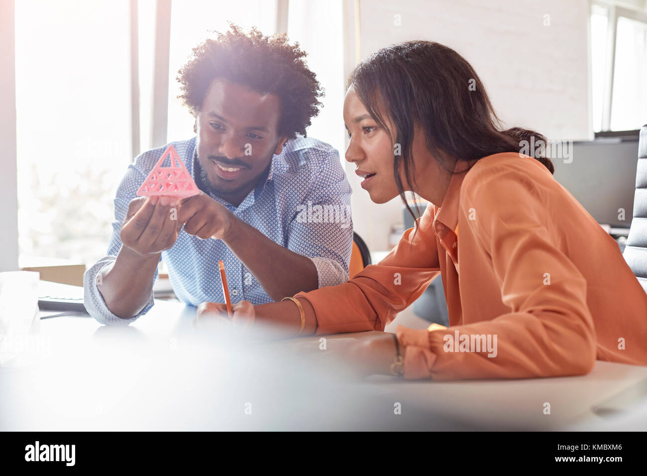 Design professionals examining triangle prototype in office - Stock Image