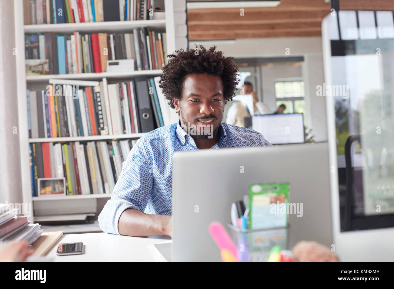 Businessman working at laptop in office - Stock Image