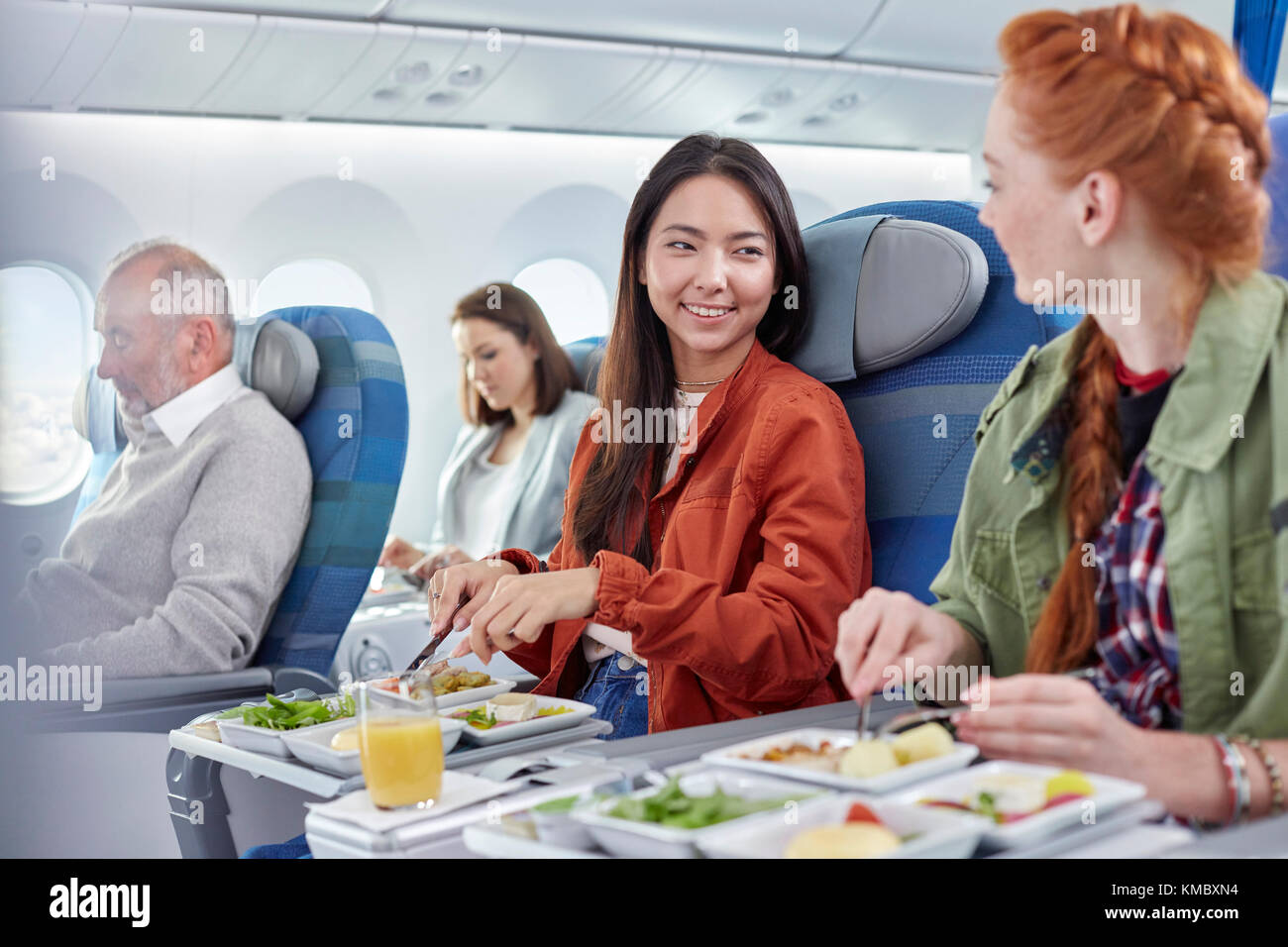Women friends eating dinner and talking on airplane - Stock Image