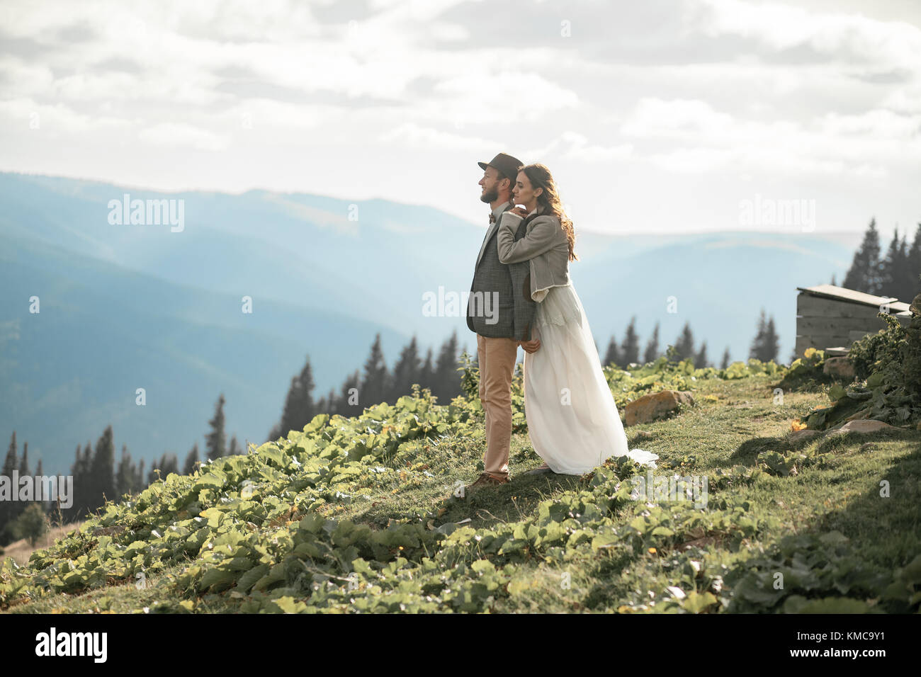 Newlyweds stand, smile and hug during honeymoon trip in Carpathian mountains. - Stock Image