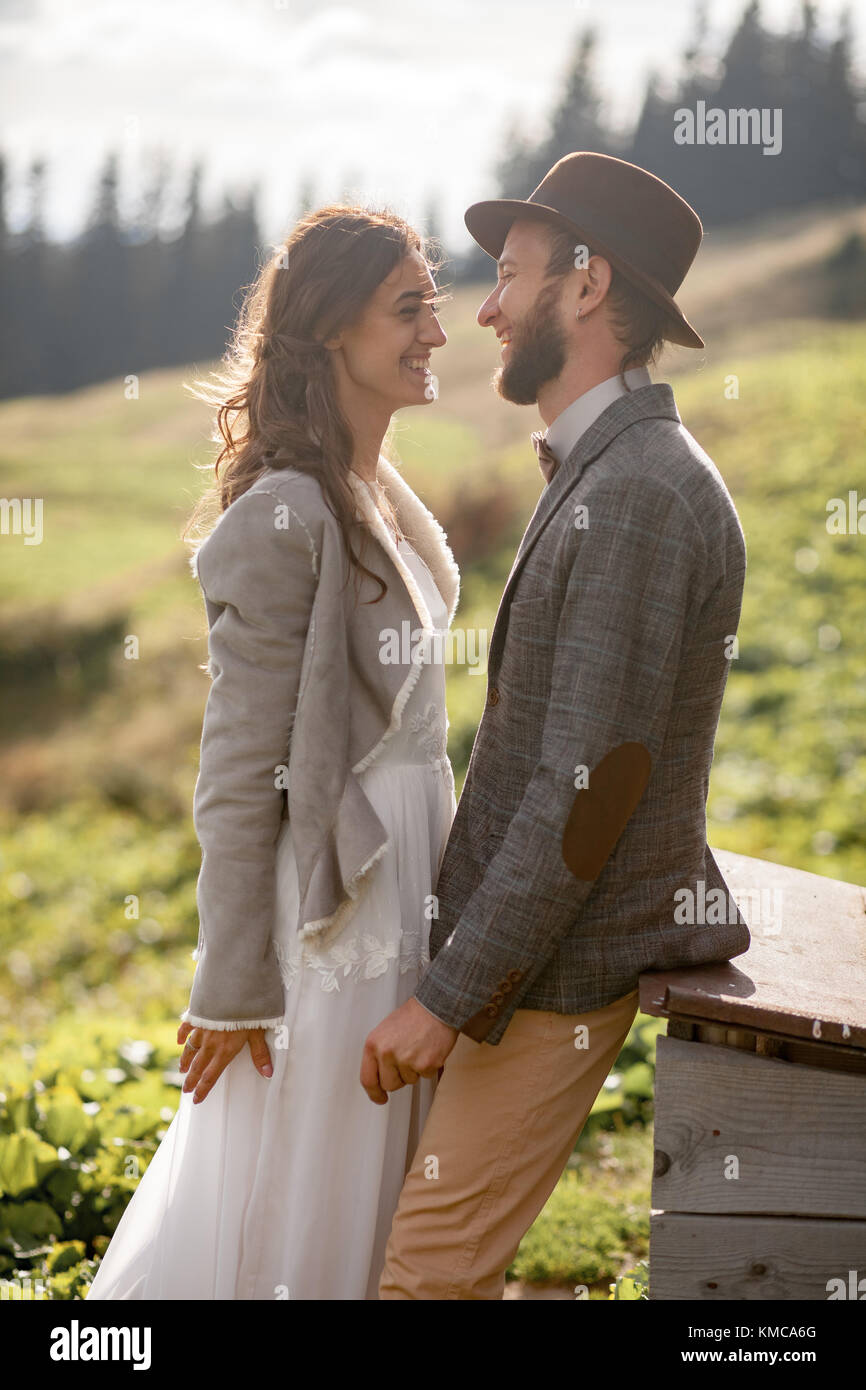 Newlyweds stand and laugh during honeymoon trip on background of Carpathian mountains. - Stock Image