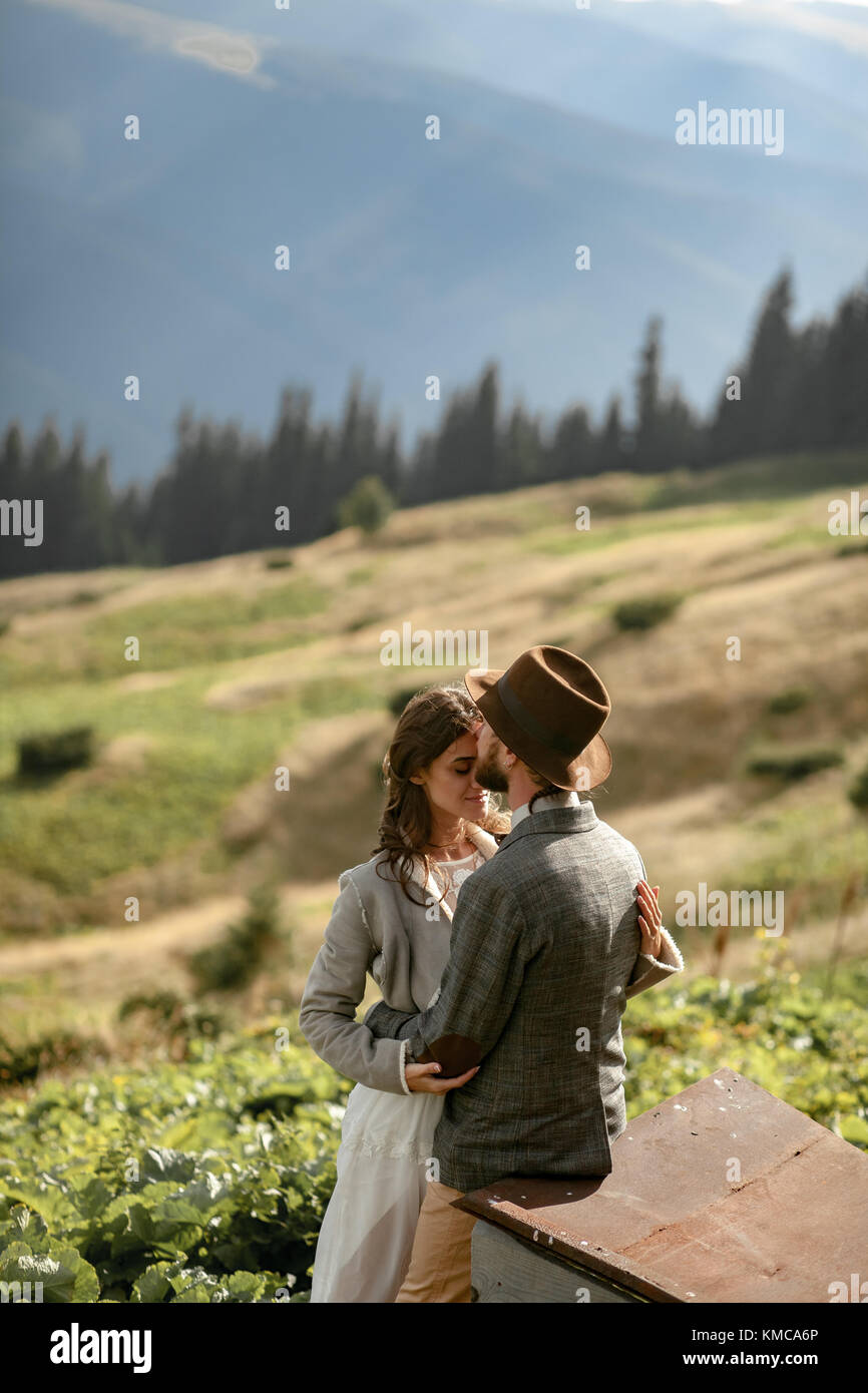 Newlyweds stand and hug during honeymoon trip on background of Carpathian mountains. - Stock Image