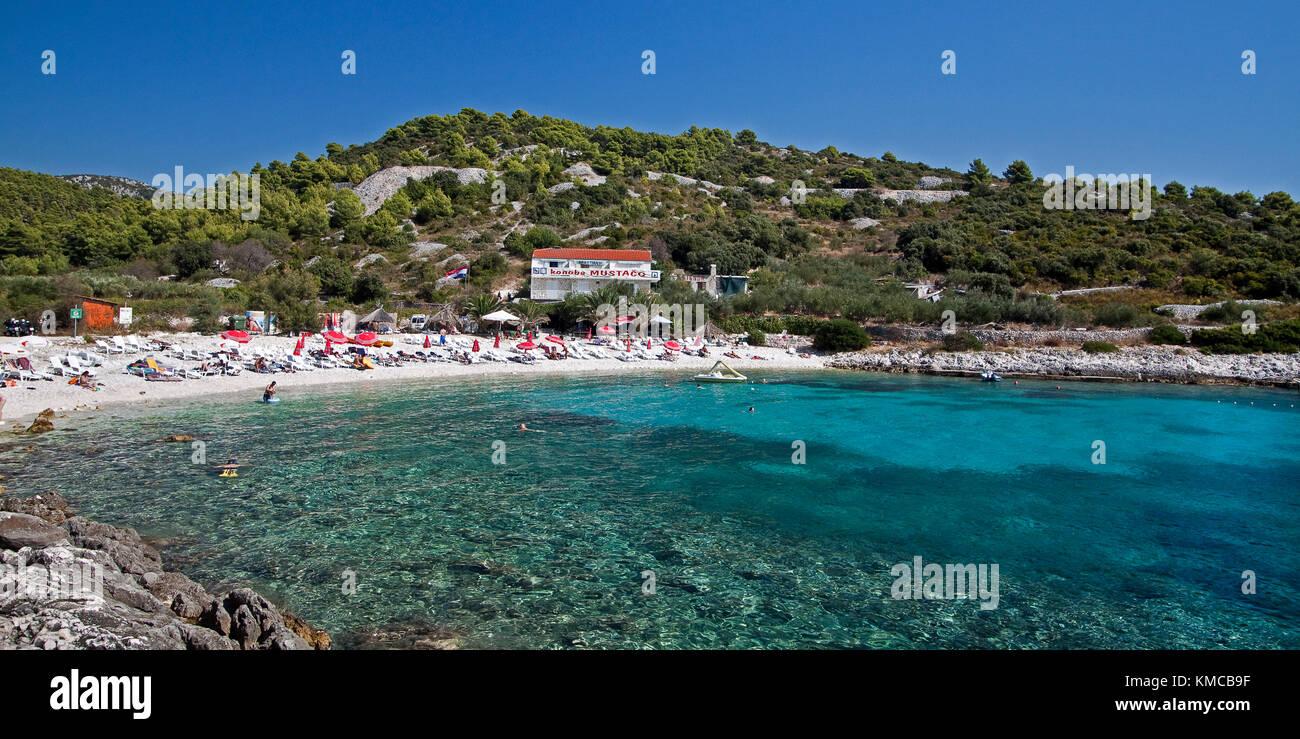 Cristal clear water at  Hvar beach  Pokonji dol with  Konoba Mustaco Restaurant , Croatia - Stock Image
