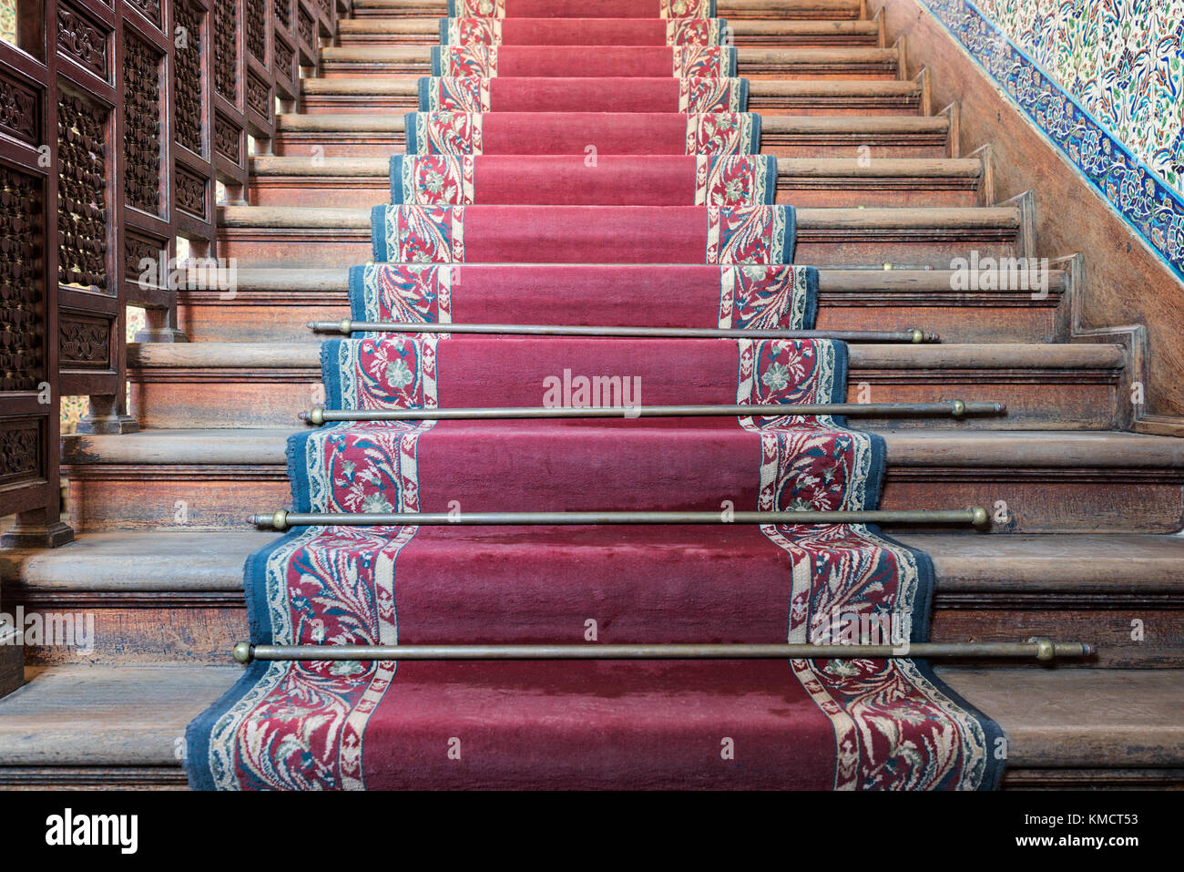 Front view of old ascending wooden stairs with ornate red carpet and wooden balustrade - Stock Image