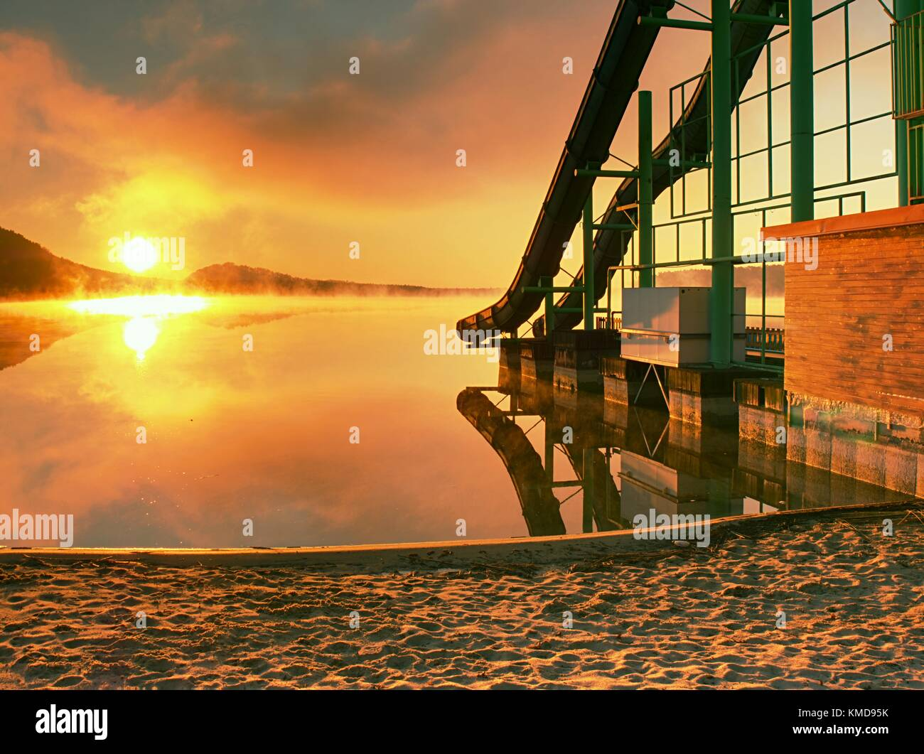 High steel tower with  sliding track on lake beach. Cold autumn morning with misty water level. End of season in - Stock Image