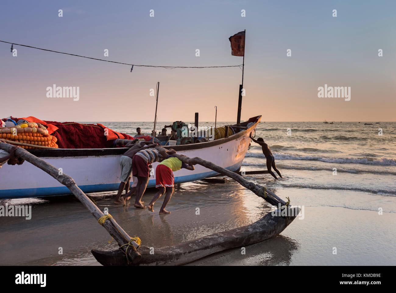 Fishermen launching their boat Colva Beach Goa India - Stock Image