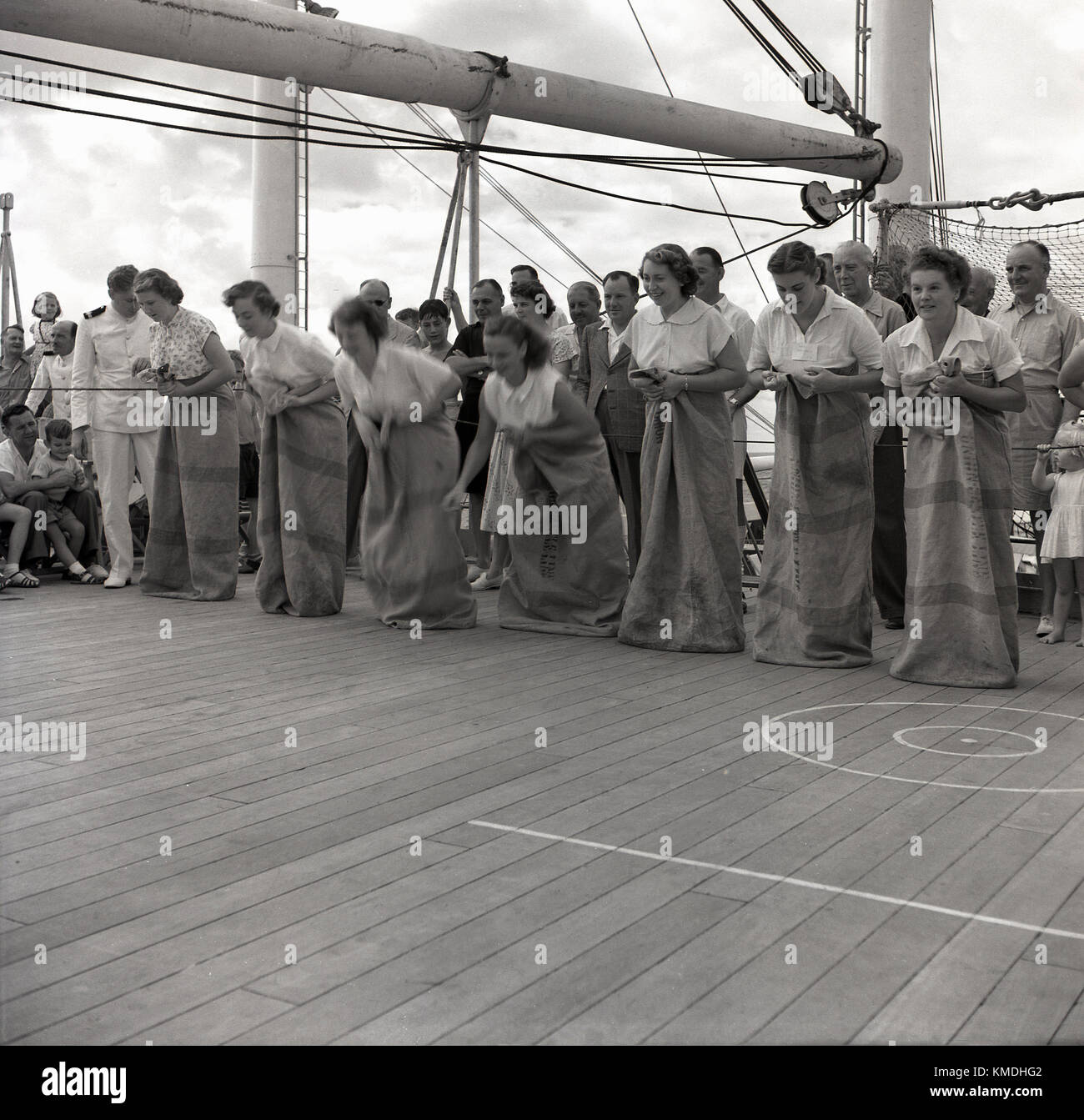 1950s, historical, ship deck games, female passengers standing in mailbags line up for a race on the deck of a Union - Stock Image
