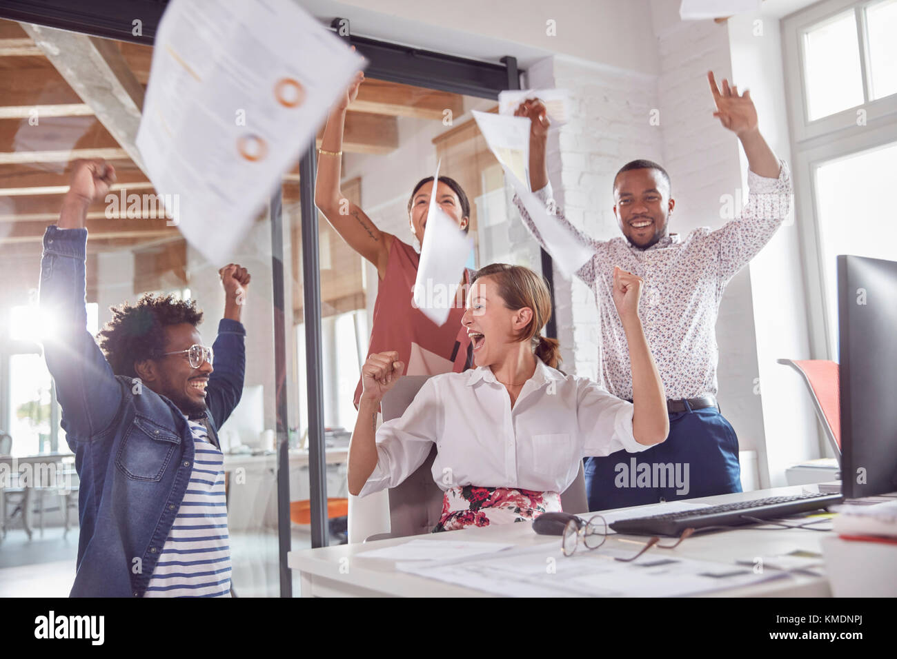 Exuberant business people celebrating,throwing paperwork overhead in office - Stock Image