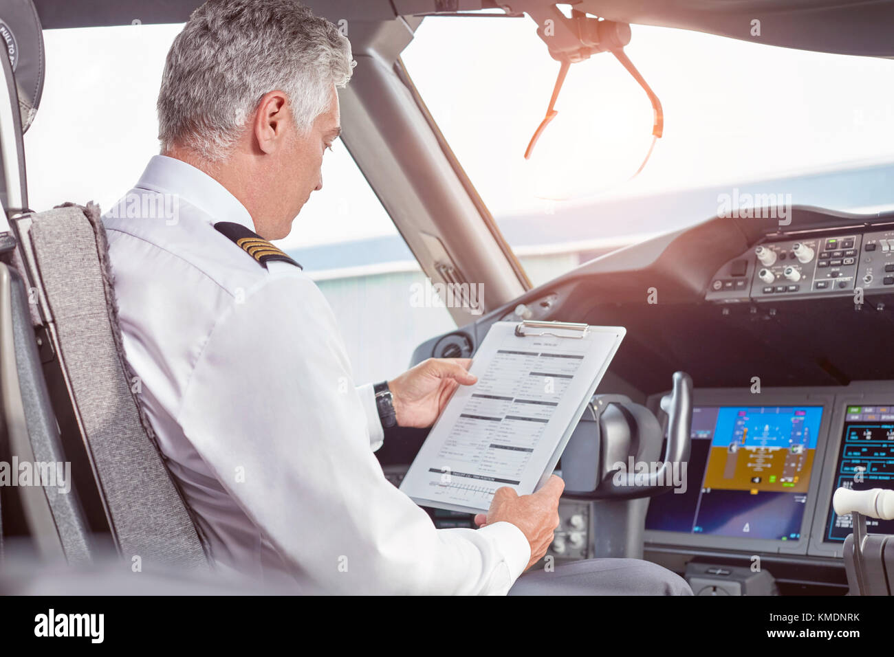 Male pilot with clipboard preparing in airplane cockpit - Stock Image