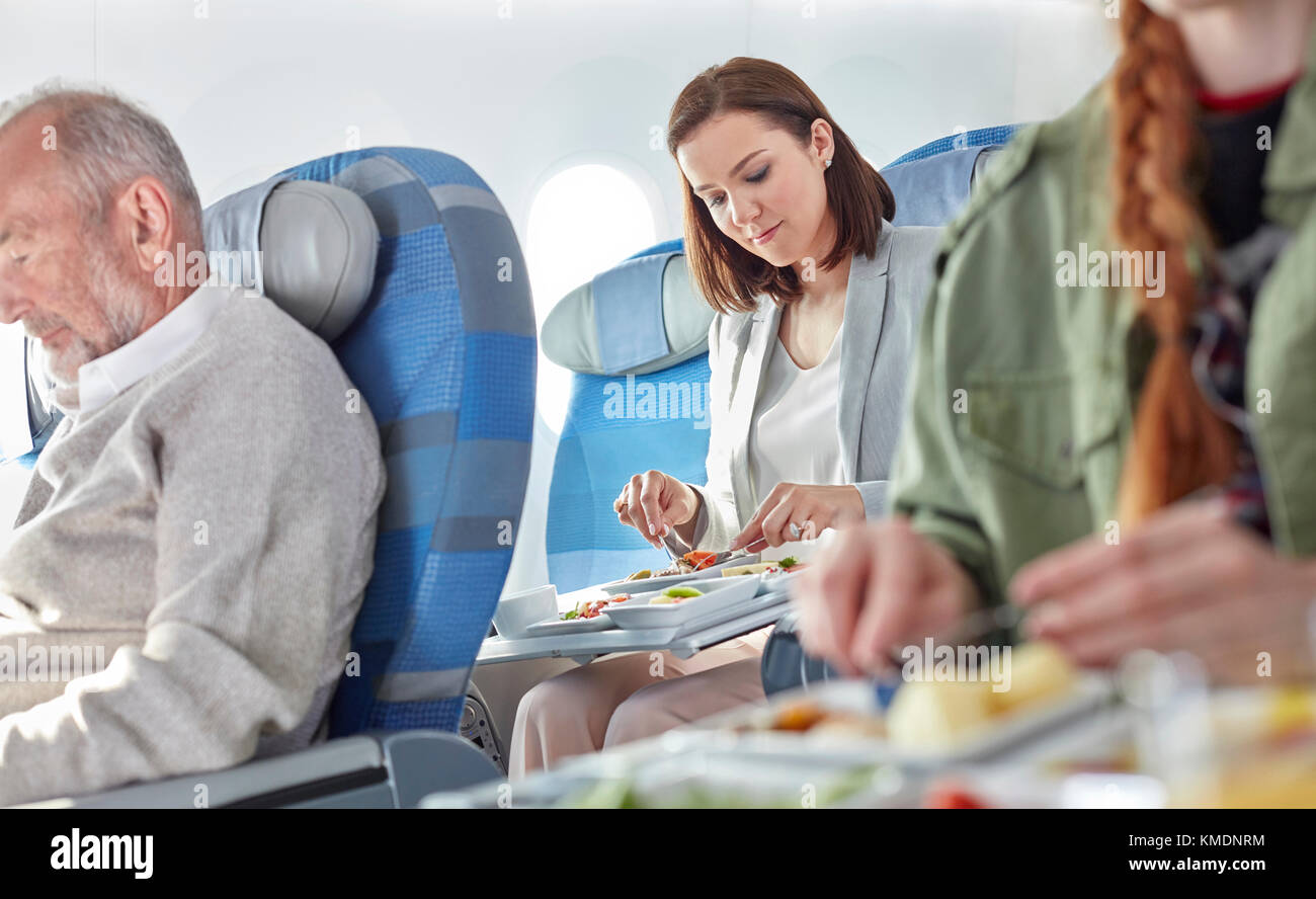 Woman eating dinner on airplane - Stock Image