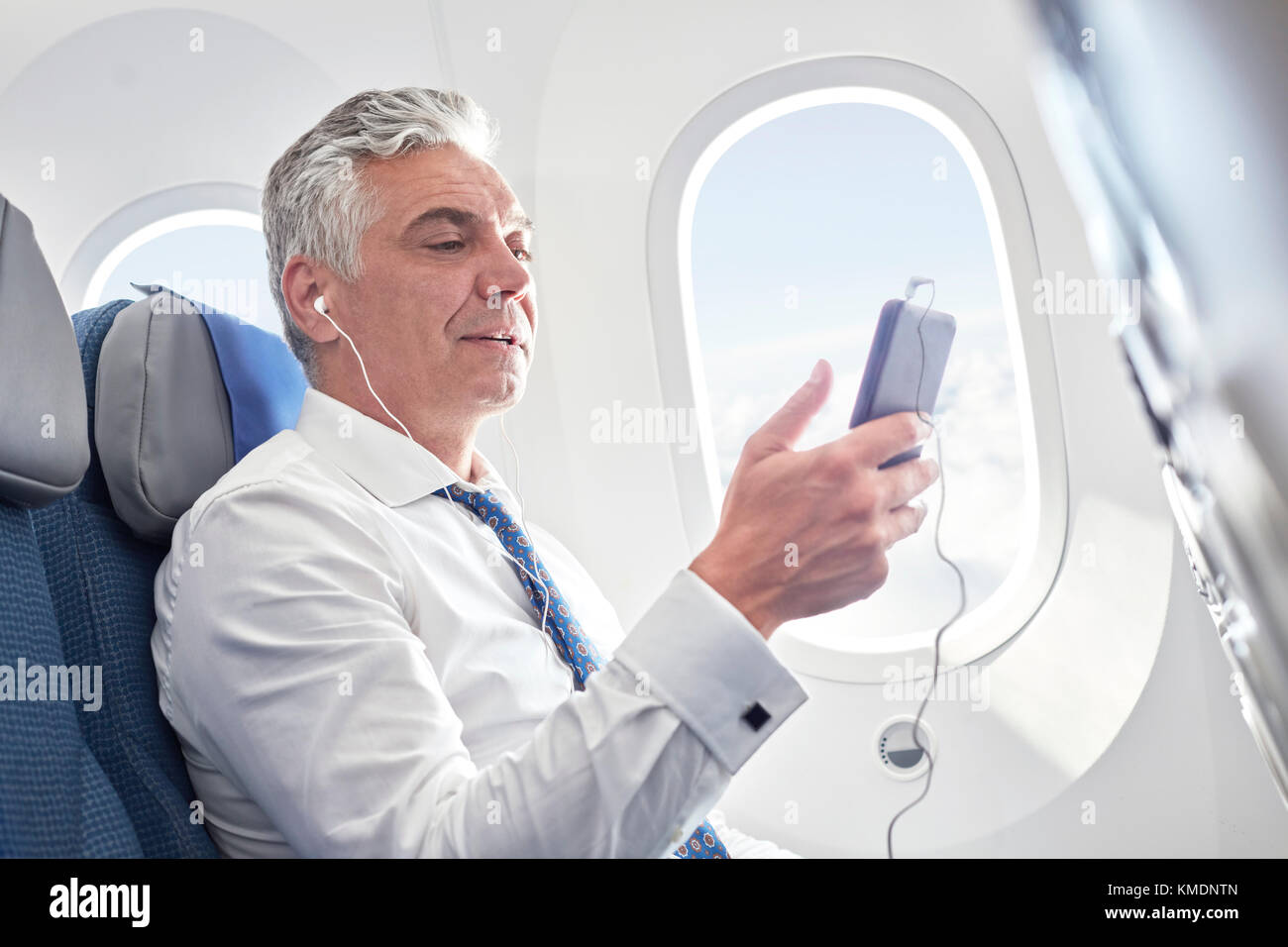 Businessman listening to music with headphones and mp3 player on airplane - Stock Image