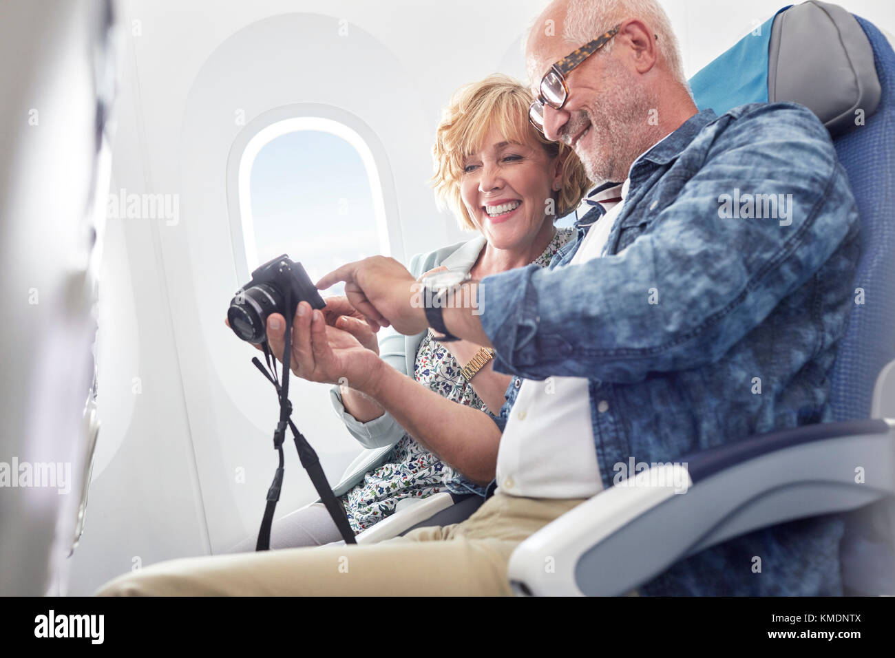 Mature couple looking at photos on digital camera on airplane - Stock Image