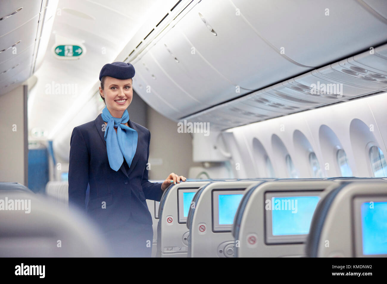 Portrait smiling,confident female flight attendant on airplane - Stock Image