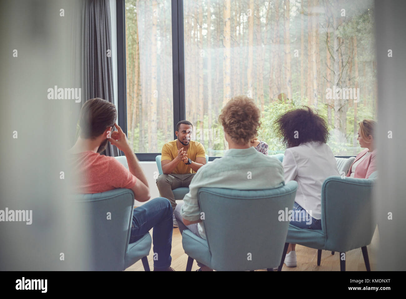 Man talking in group therapy session - Stock Image