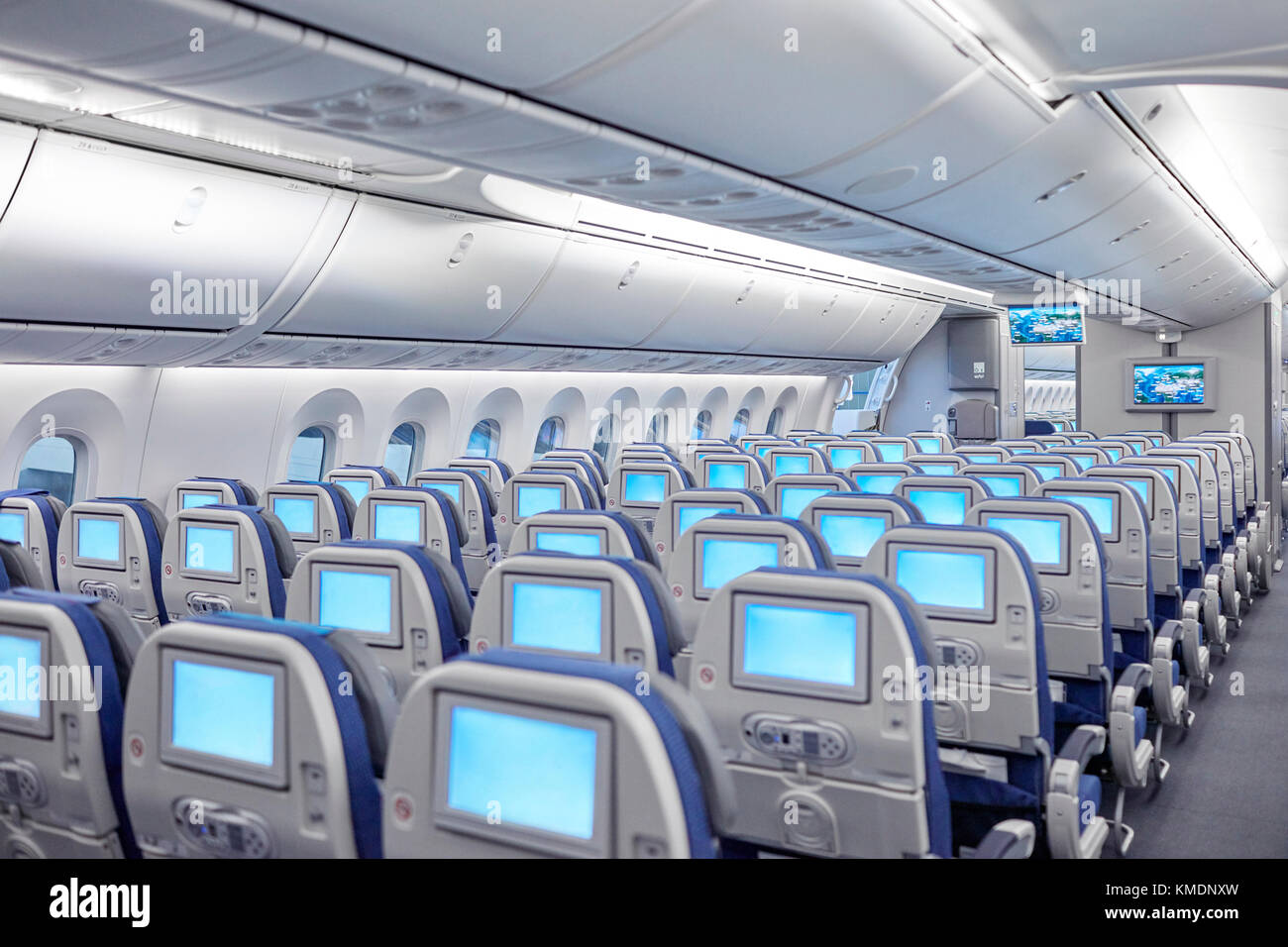Rows of seats with entertainment screens on airplane - Stock Image