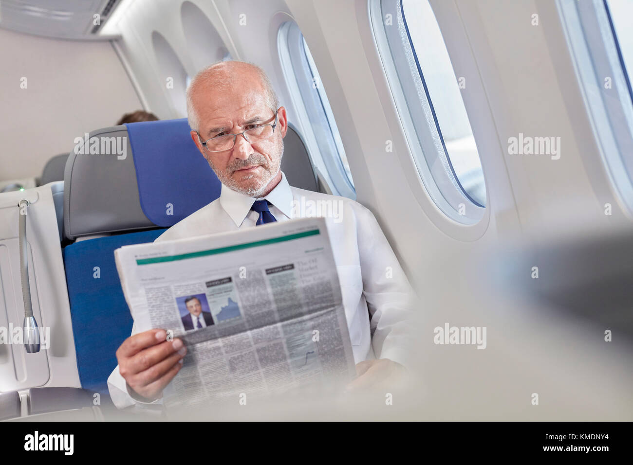 Businessman reading newspaper on airplane - Stock Image