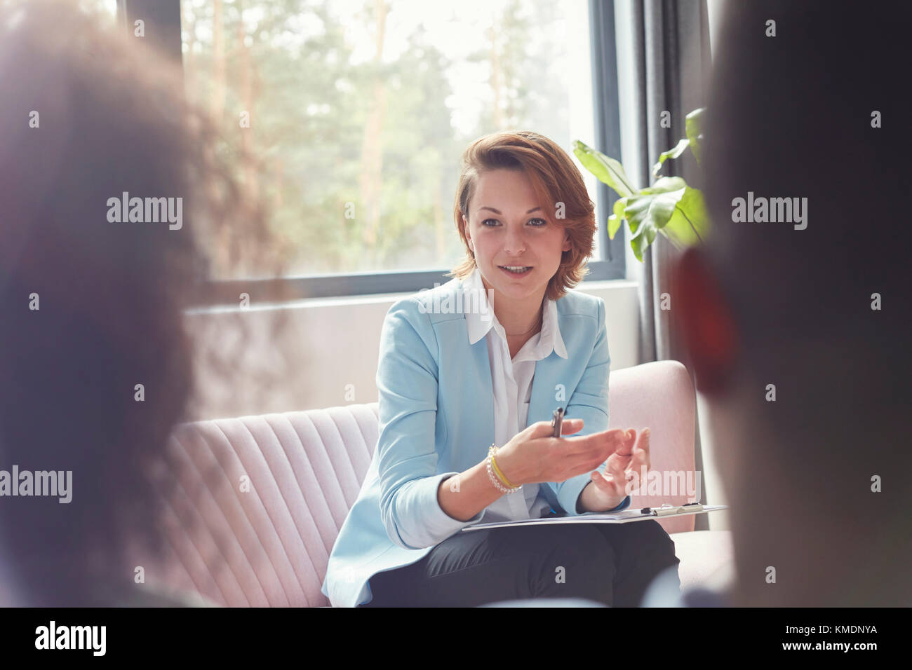Female therapist talking to couple in couples therapy session - Stock Image