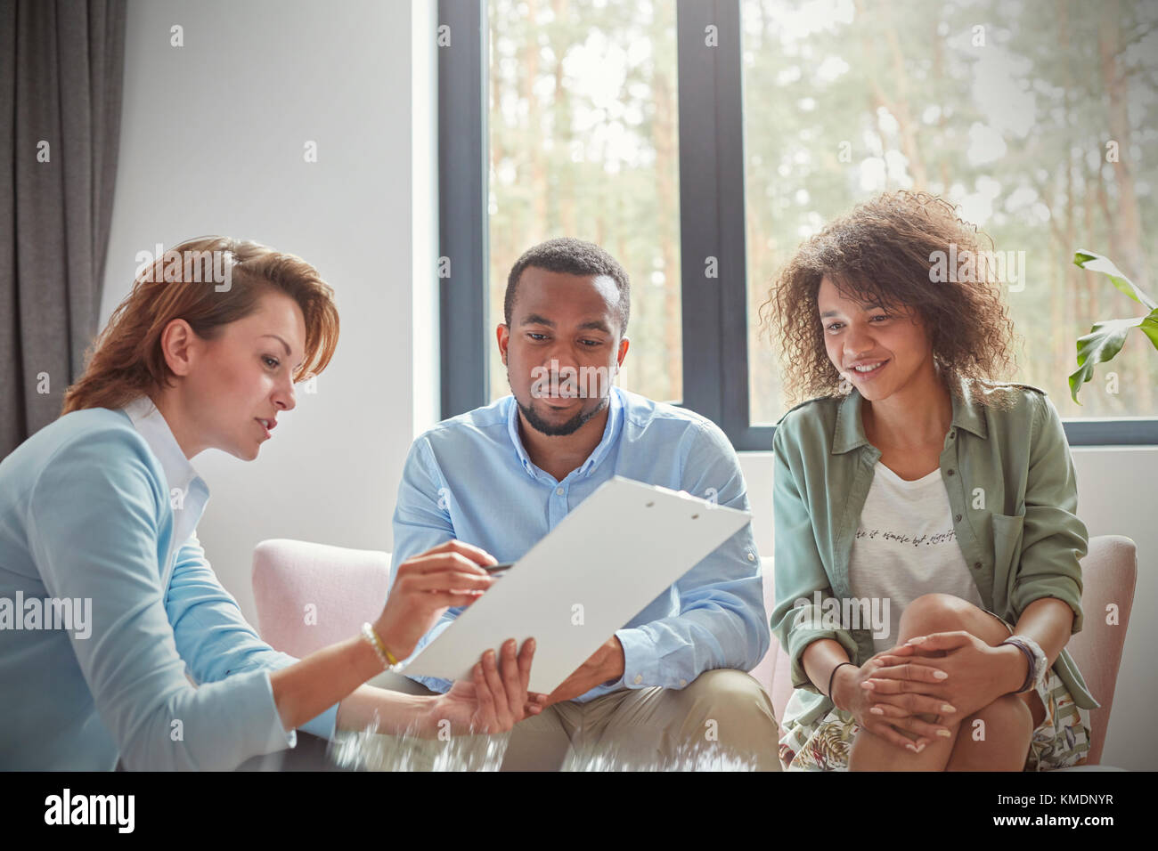 Female therapist with clipboard talking to couple in couples therapy session - Stock Image