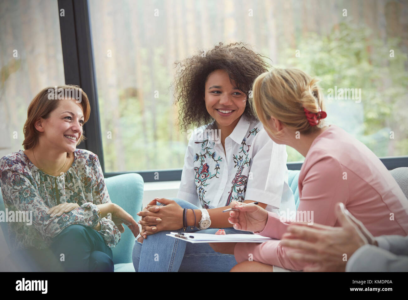 Smiling women talking in group therapy session - Stock Image