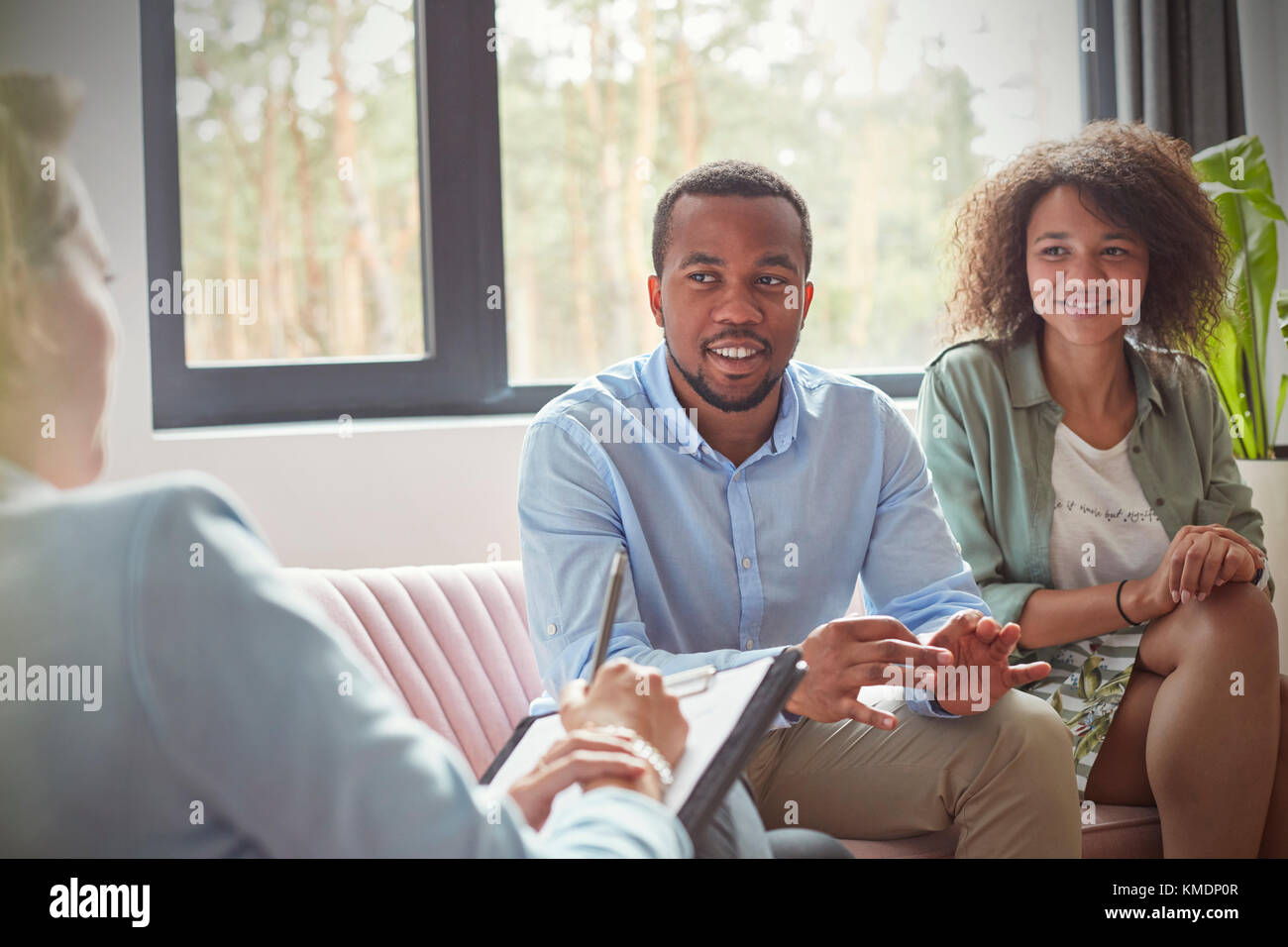 Couple listening to female therapist in couples therapy counseling session - Stock Image