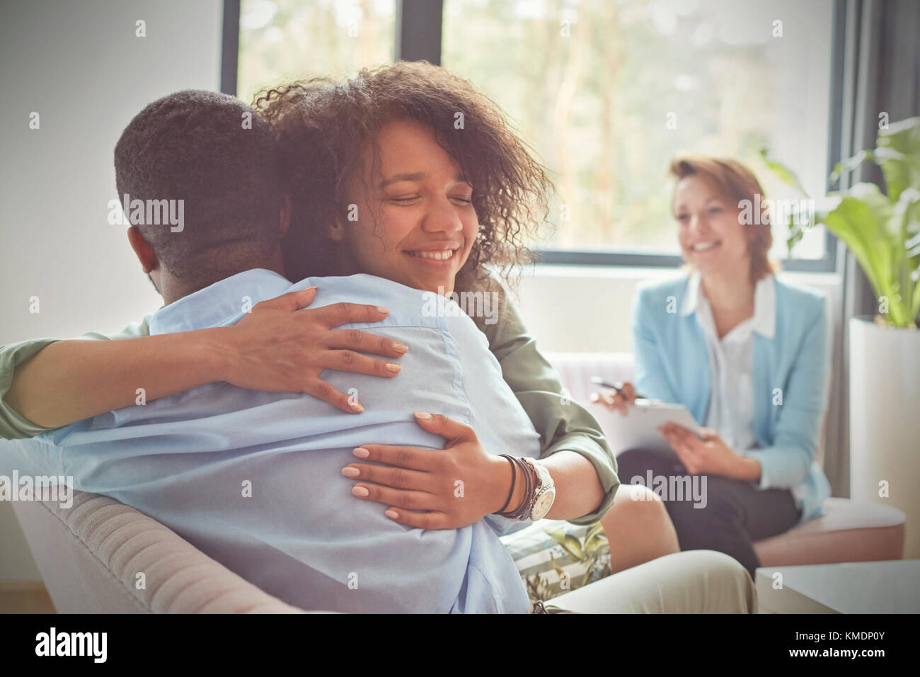 Smiling female therapist watching couple hugging in couples therapy session - Stock Image