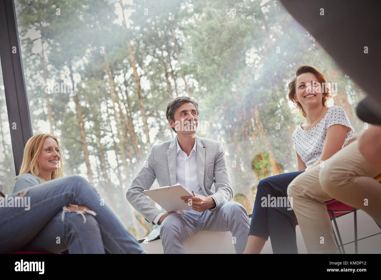 Smiling people talking in group therapy session - Stock Image