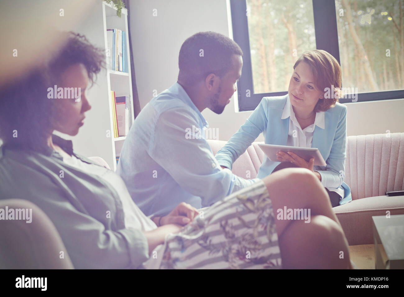 Female therapist with digital tablet comforting man in couples therapy session - Stock Image