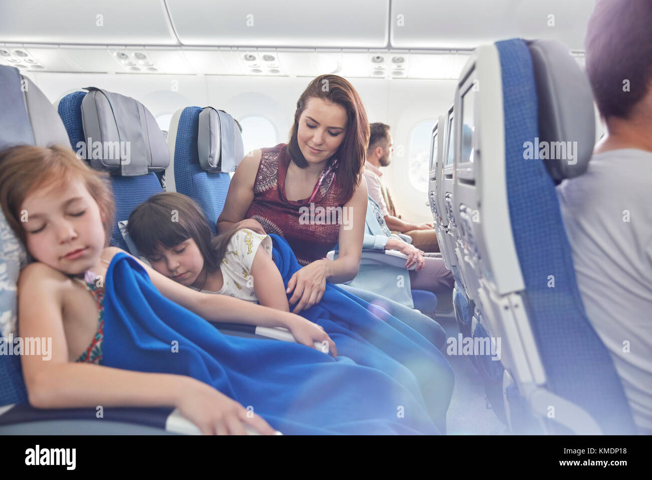 Mother putting blanket on sleeping daughter on airplane - Stock Image