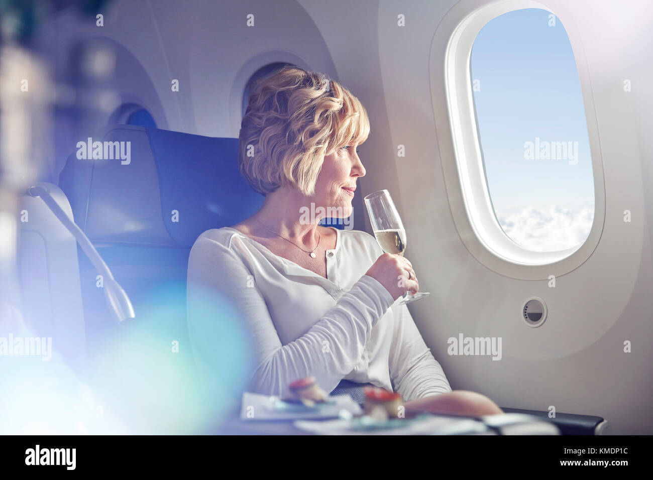 Mature woman drinking champagne,looking out window in first class on airplane - Stock Image
