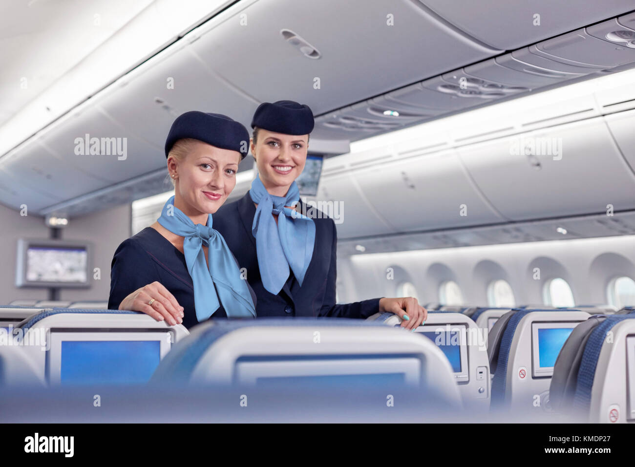 Portrait smiling,confident female flight attendants on airplane - Stock Image