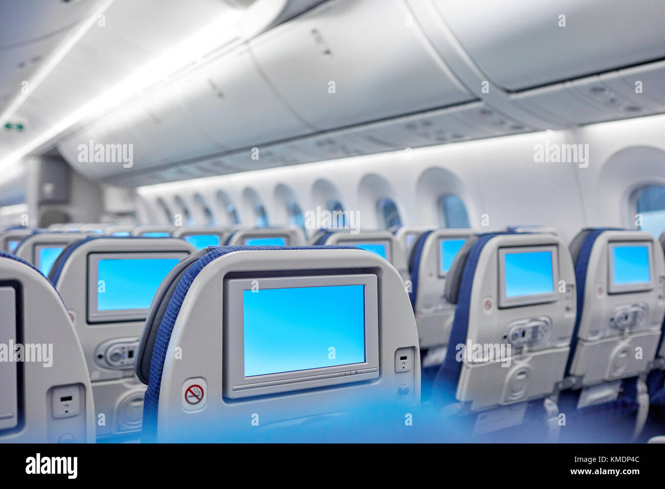 Entertainment screens on seats in airplane - Stock Image