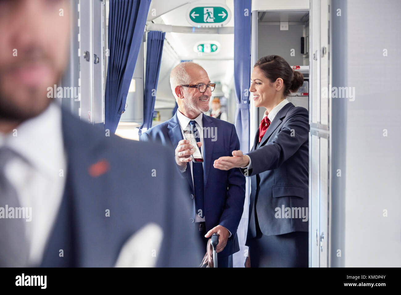 Flight attendant helping businessman with digital boarding pass on airplane - Stock Image