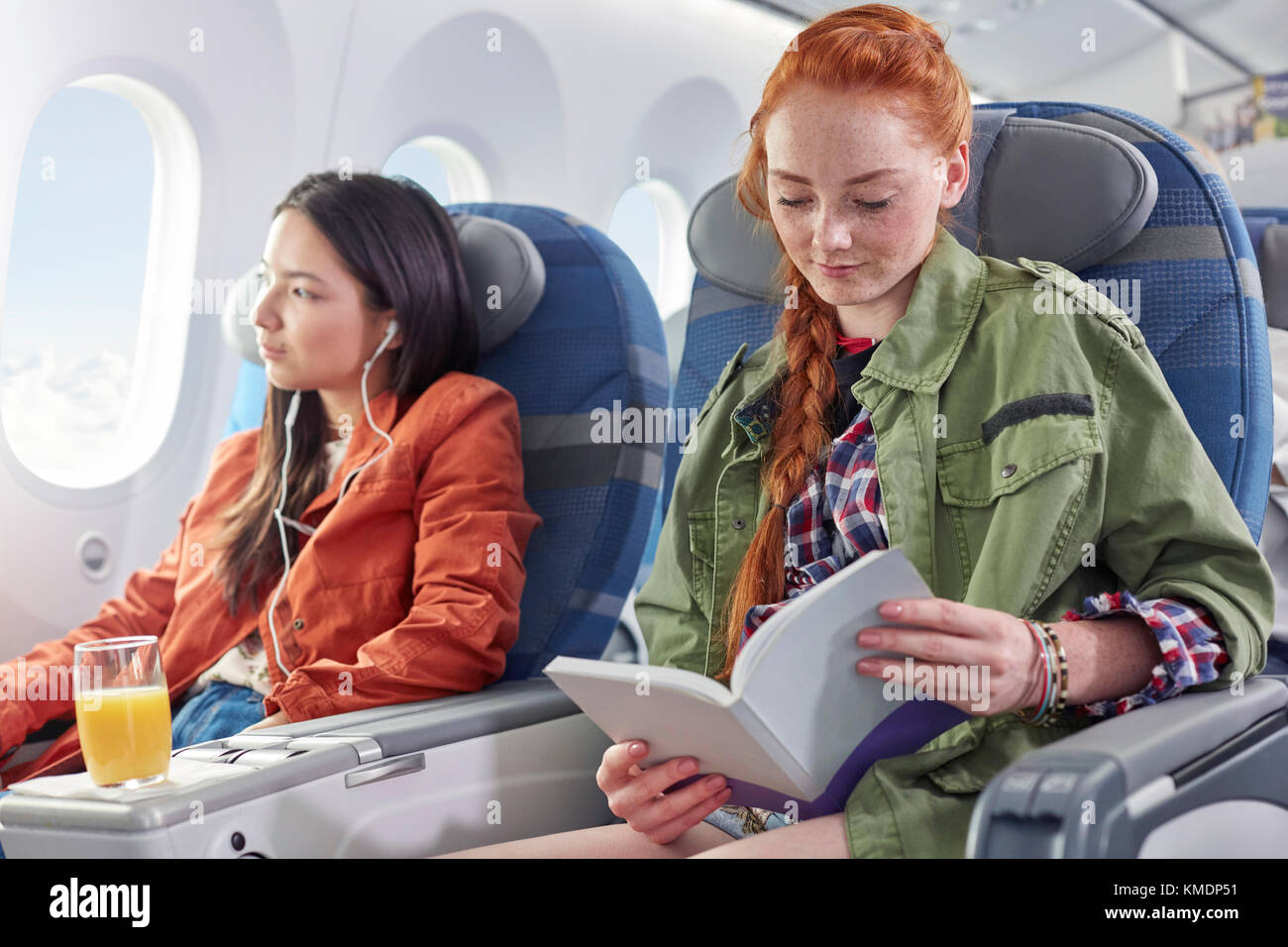Young woman reading book on airplane - Stock Image