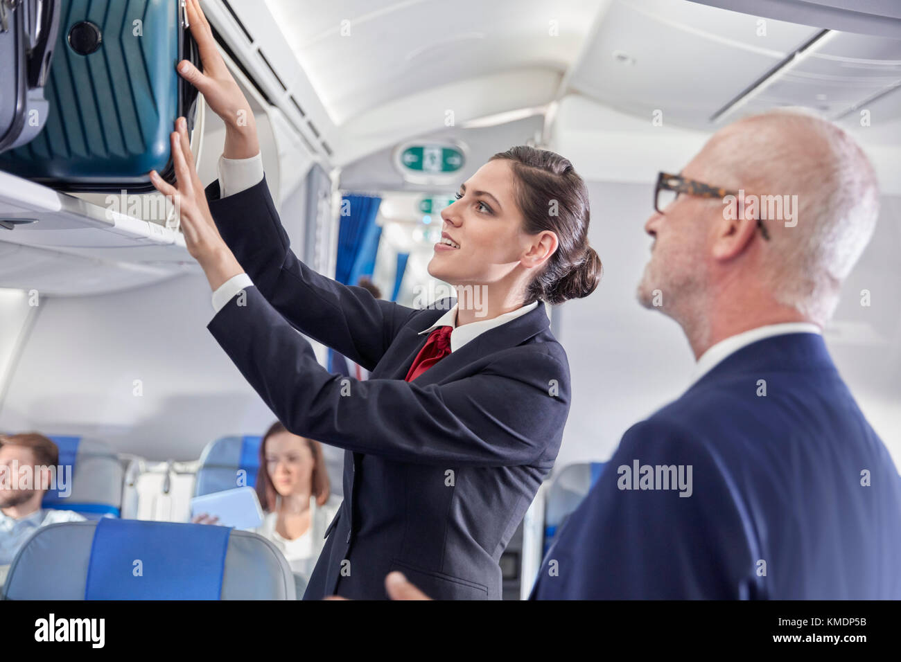 Flight attendant helping businessman place luggage in overhead compartment on airplane - Stock Image