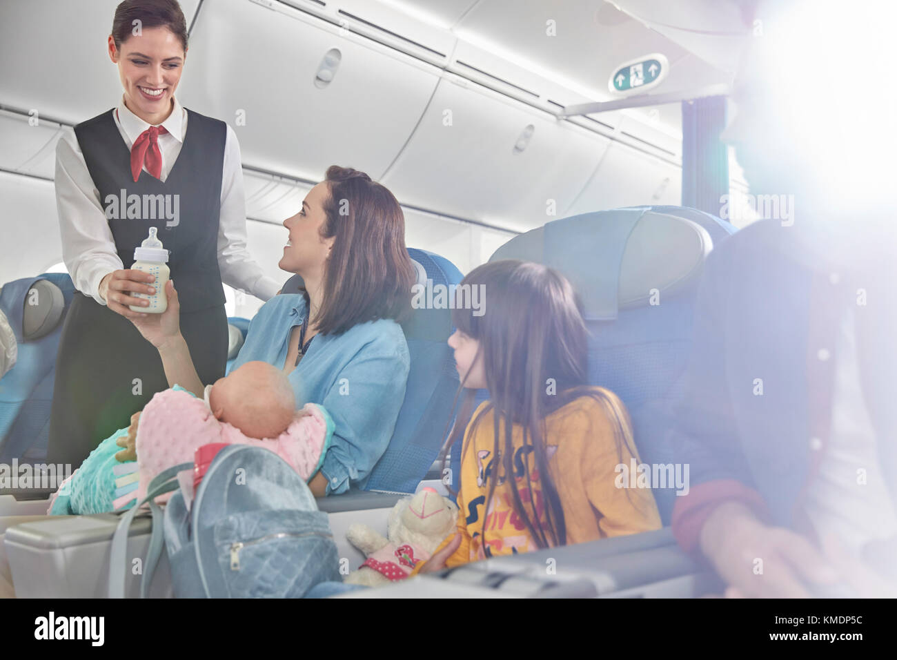 Smiling flight attendant bringing baby bottle to mother with baby on airplane - Stock Image
