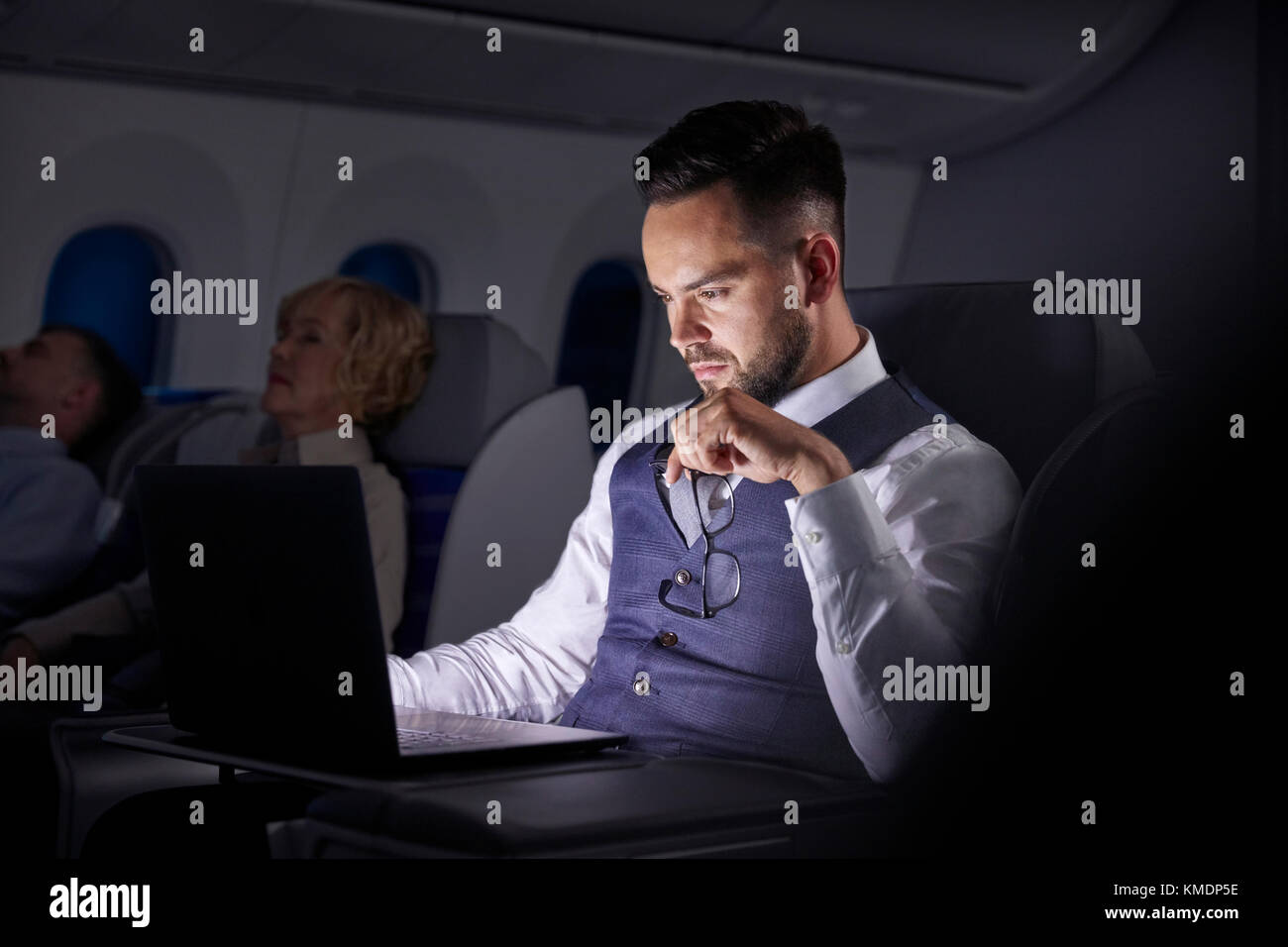 Serious businessman working at laptop on overnight airplane - Stock Image