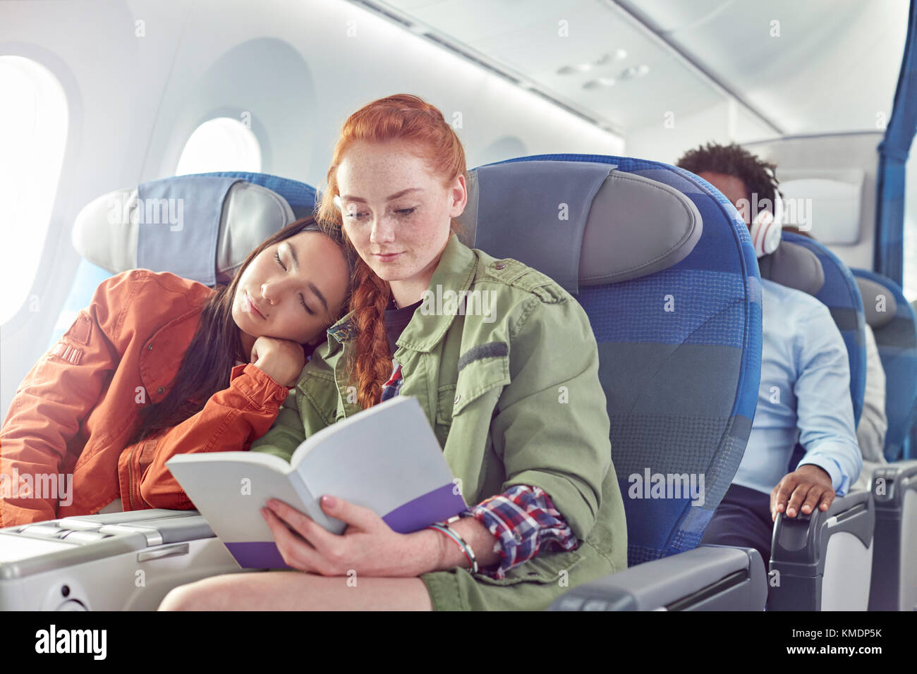 Affectionate young lesbian couple sleeping and reading on airplane - Stock Image