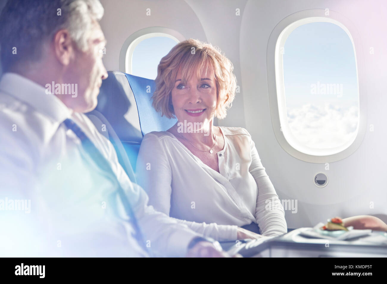 Businessman and businesswoman talking in first class on airplane - Stock Image