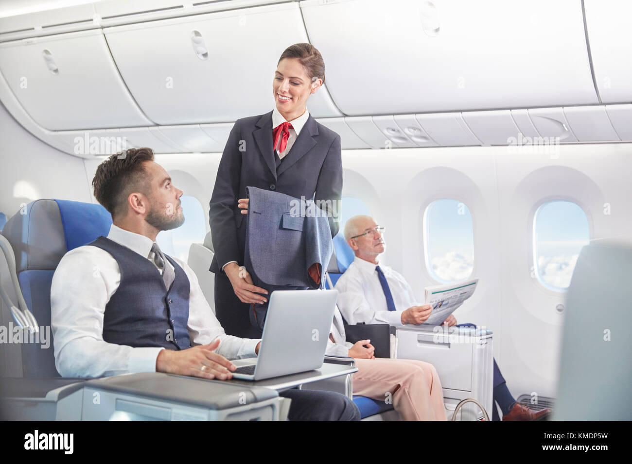 Flight attendant talking with businessman working at laptop on airplane - Stock Image