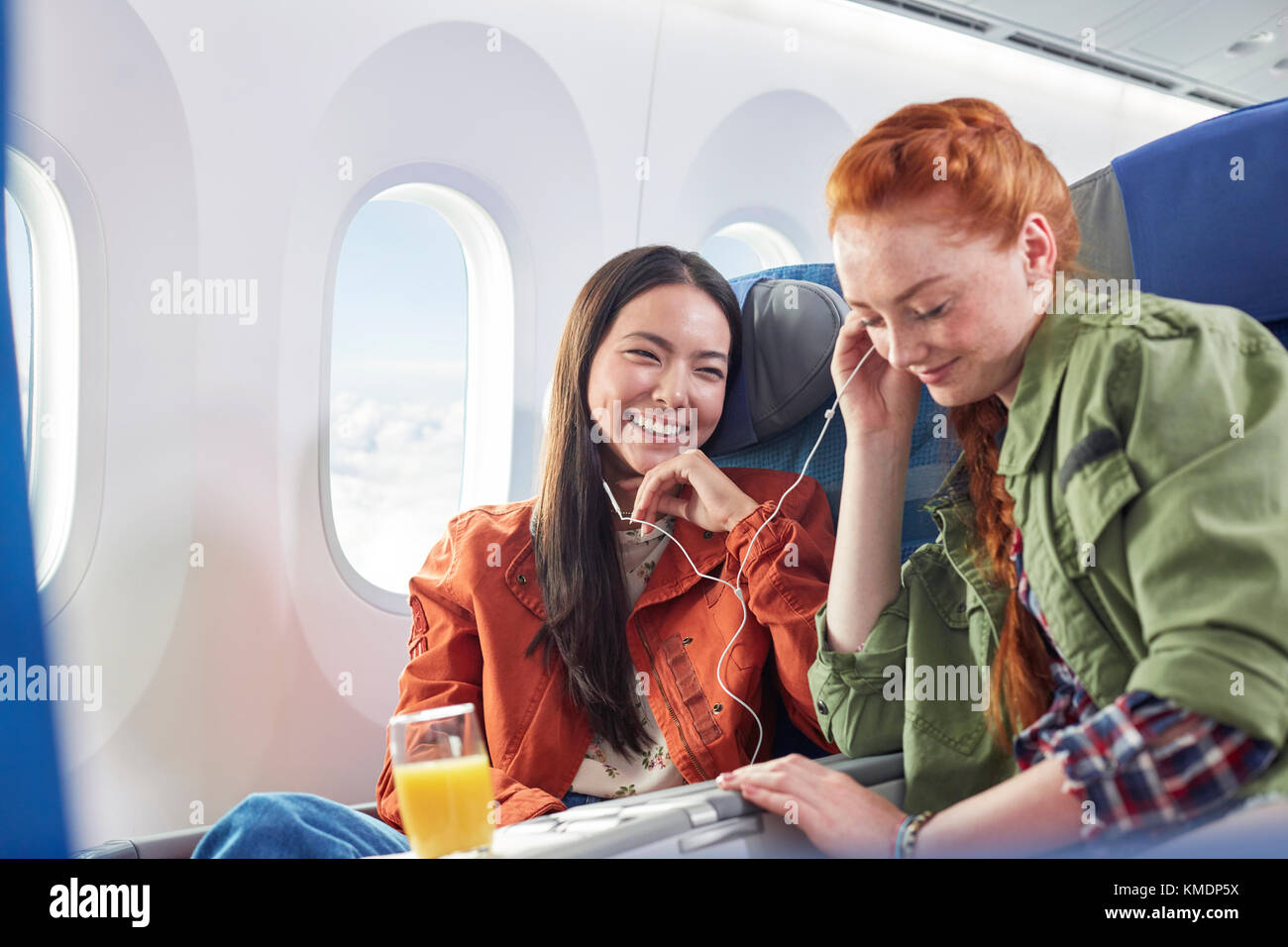 Young women friends sharing headphones,listening to music on airplane - Stock Image