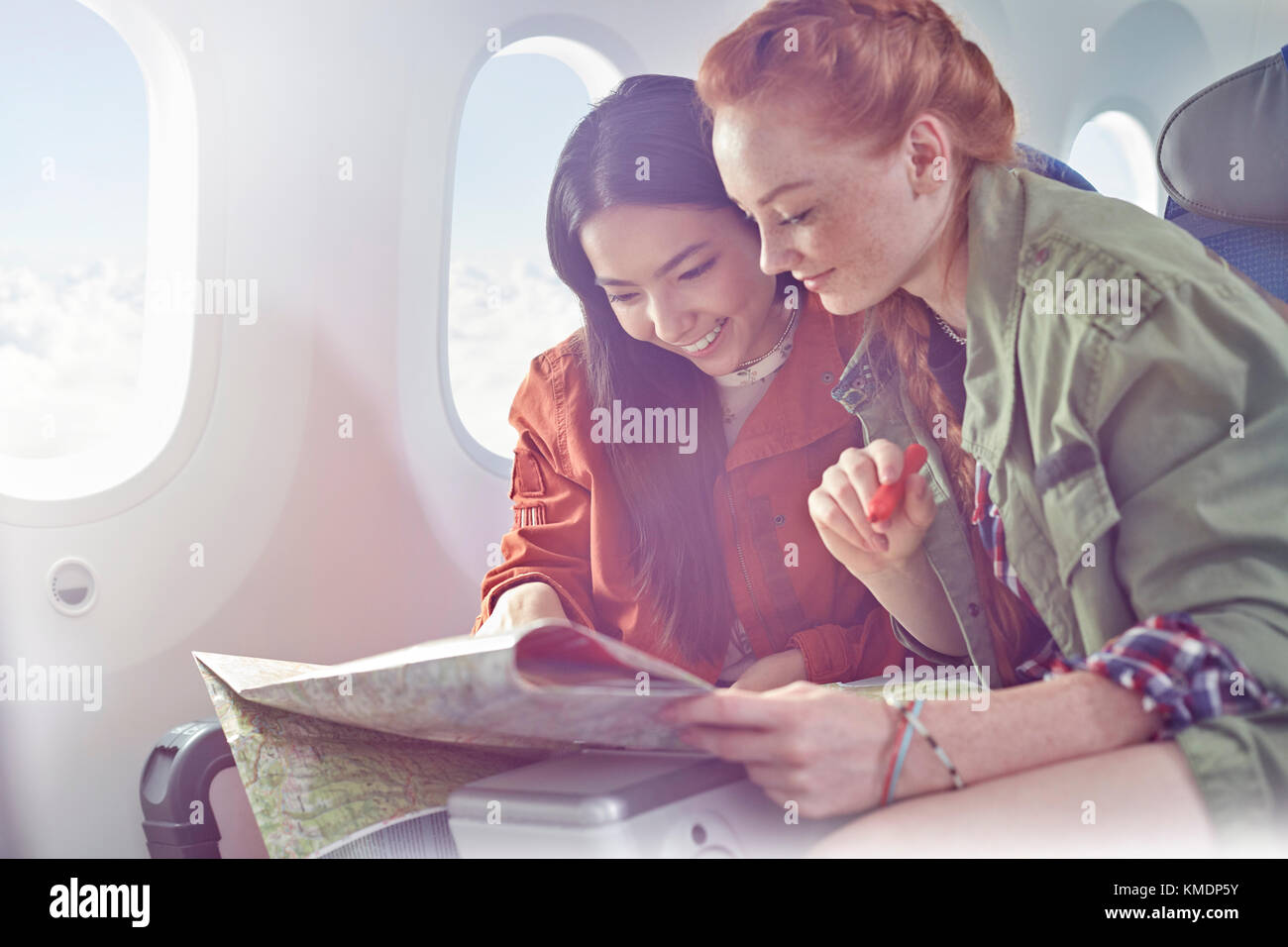 Young women friends looking at map on airplane - Stock Image