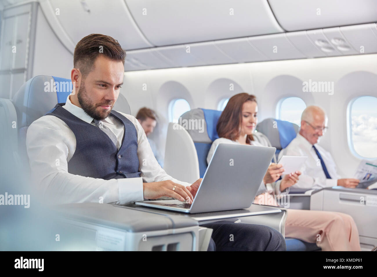 Businessman working at laptop on airplane - Stock Image