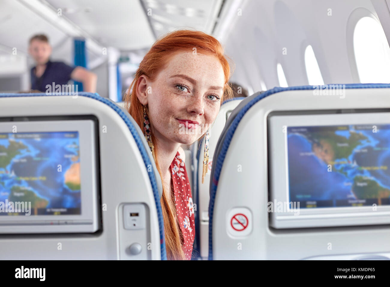 Portrait smiling young woman with red hair and freckles on airplane - Stock Image