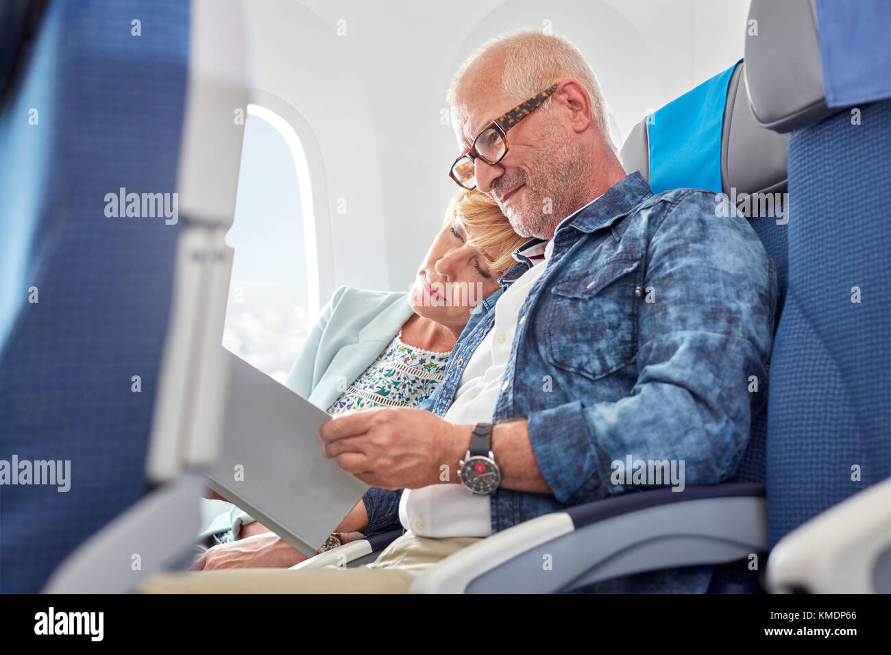 Affectionate mature couple sleeping and reading on airplane - Stock Image