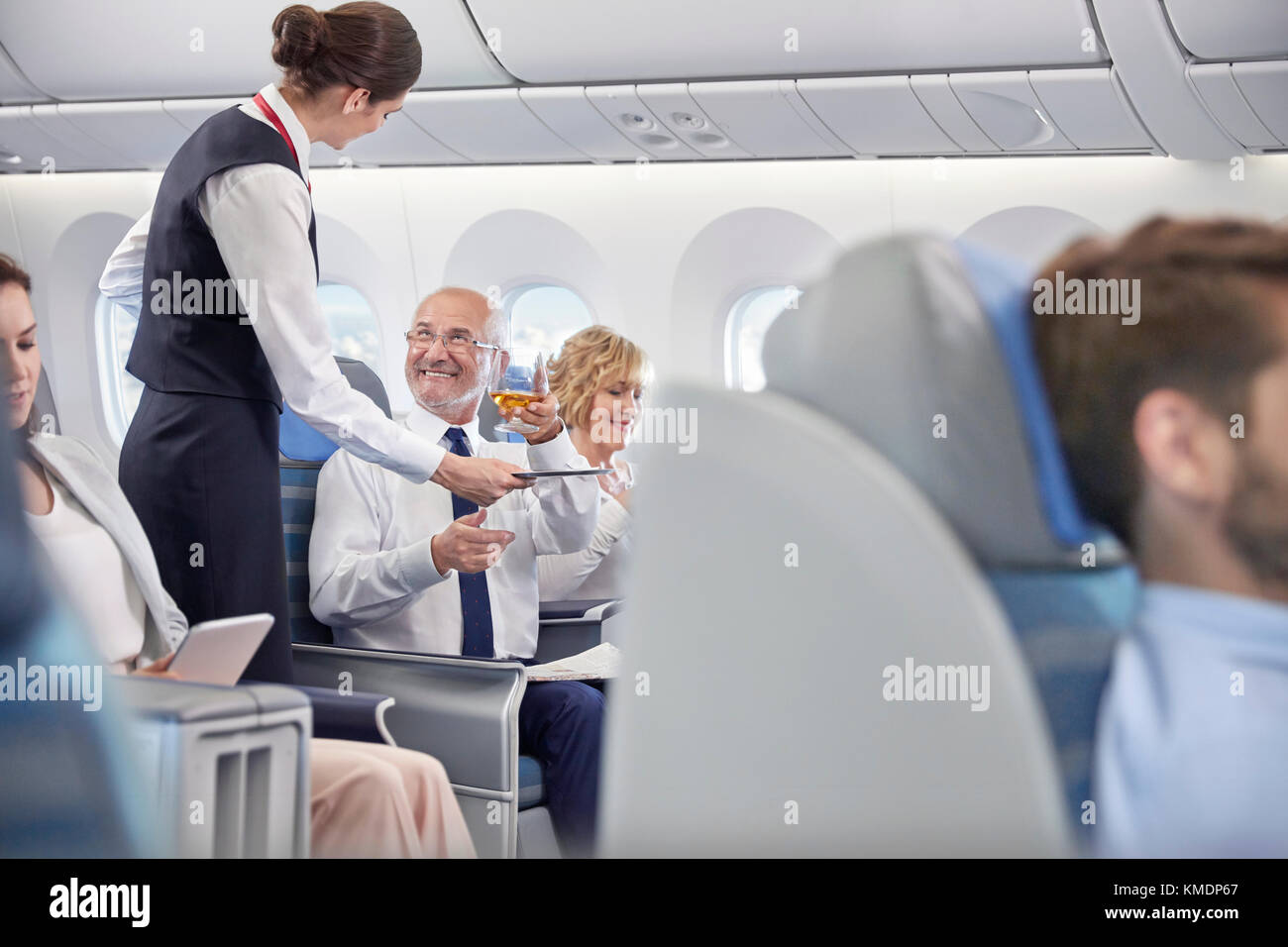 Flight attendant serving whiskey to businessman in first class on airplane - Stock Image