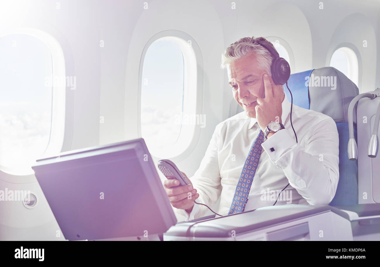 Businessman with headphones watching movie on airplane - Stock Image