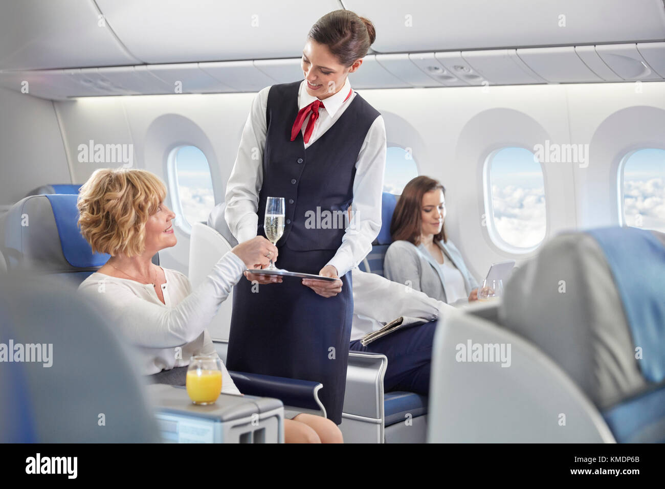 Flight attendant serving champagne to woman in first class on airplane - Stock Image